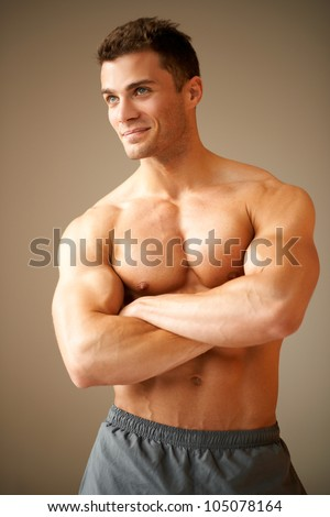 Smiling handsome man with muscular arms crossed looking his right - stock photo
