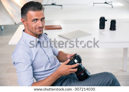 Smiling handsome photographer using camera and looking at camera in studio - stock photo