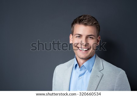 Smiling handsome vivacious happy young man in a jacket posing against a dark background with copyspace, head and shoulders portrait - stock photo