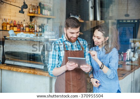 Smiling handsome waiter holding tablet and young pretty woman pointing on it in coffee shop - stock photo