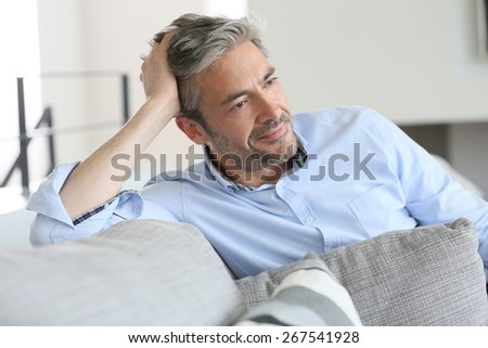 Smiling handsome 45-year-old man relaxing at home - stock photo
