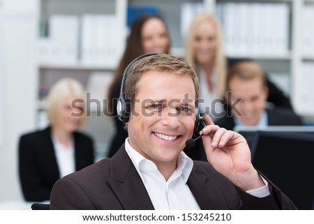 Smiling handsome young businessman using a headset in the office to facilitate hands free communication or answering calls at a call centre - stock photo