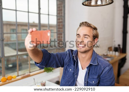 Smiling Handsome Young Man Taking Self Picture Using Mobile Phone Inside the House. - stock photo