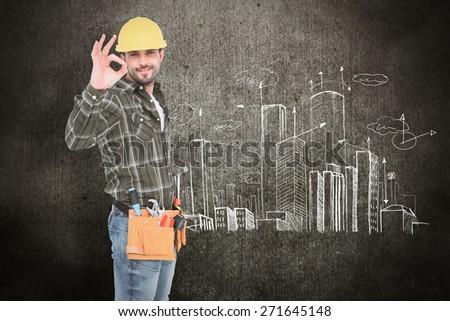 Smiling handyman gesturing okay against hand drawn city plan - stock photo