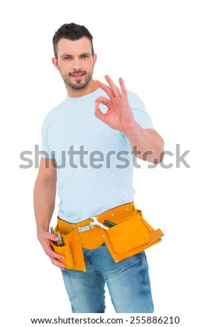 Smiling handyman gesturing okay on white background - stock photo
