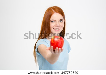 Smiling happy attractive lady with long red hair holding an apple and offer it to you over white background - stock photo