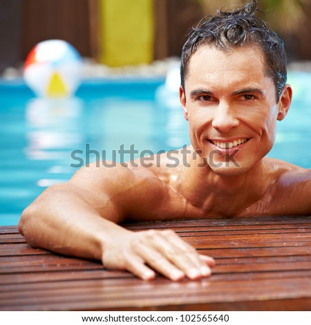 Smiling happy attractive man in a swimming pool - stock photo