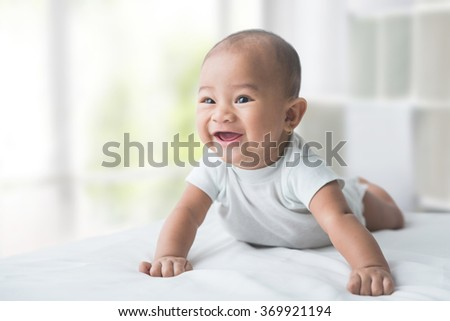 smiling happy baby while tummy time at home
