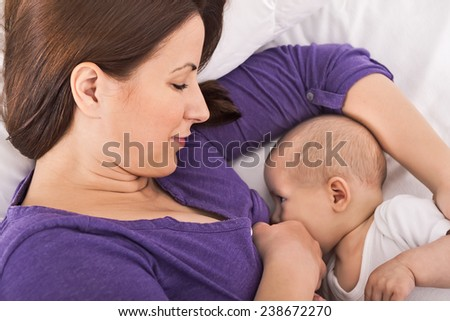 Smiling happy beautiful mother breastfeeding her baby infant - stock photo