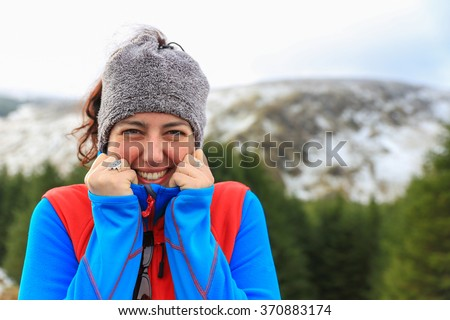 Smiling happy beautiful woman wearing colorful warm winter clothes standing in a snowy white mountain landscape in Ireland holding her face