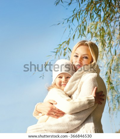 Smiling happy blonde woman and girl hugging outdoor in park against blue sky, mother and daughter. - stock photo