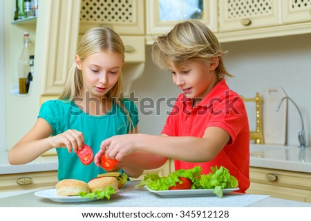 smiling happy boy and girl making homemade hamburgers or sandwiches - stock photo