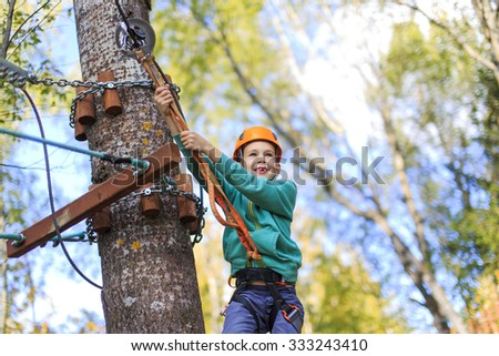 Smiling happy boy in rope park. a child wearing a safety belt and helmet overcomes obstacles in the rope park and enjoy it. - stock photo