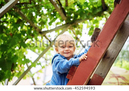 Smiling happy boy on the wooden stairs