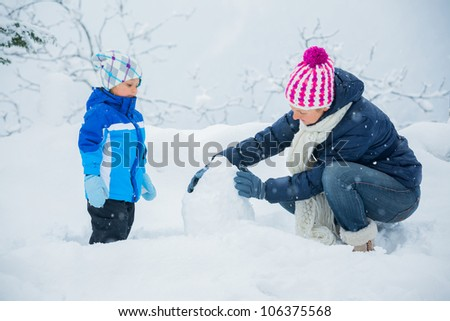Smiling happy boy with his mother having fun outdoors on snowing winter day in Alps playing in snow. - stock photo