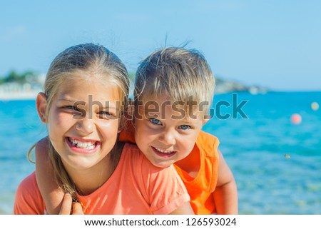 Smiling happy brother and sister posing on a beach. In the background the sea - stock photo