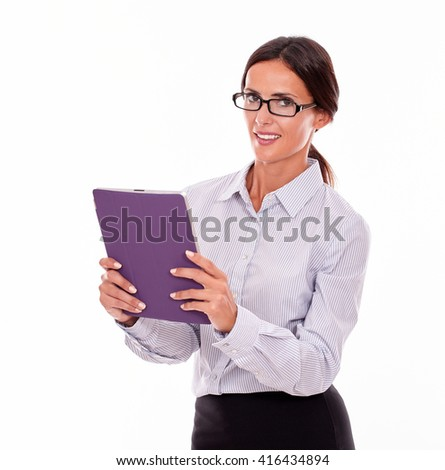 Smiling happy brunette businesswoman with glasses carrying a tablet, wearing her straight hair tied back and a button down shirt while looking at the camera on a white background - stock photo