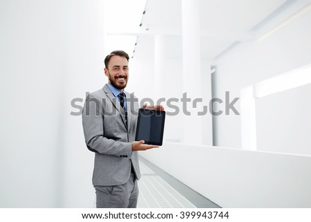 Smiling happy businessman is holding portable digital tablet with blank copy space screen for your advertising text message. Cheerful male entrepreneur with touch pad in hands is standing in office - stock photo