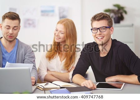 Smiling happy businessman wearing glasses in a meeting with two young colleagues at the office as they discuss paperwork