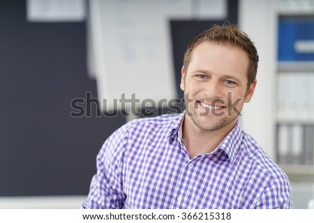 Smiling happy confident businessman looking at the camera with a warm beaming smile, close up head and shoulders with copy space - stock photo