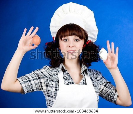 Smiling happy cook woman holds a easter eggs - stock photo