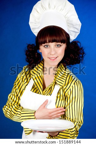 Smiling happy cook woman holds a plate on a blue background - stock photo