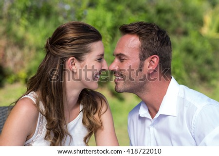 Smiling happy couple face to face in park - stock photo