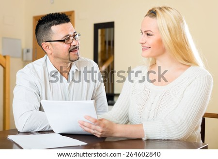 Smiling happy couple filling in a questionnaire sitting at the table at home - stock photo