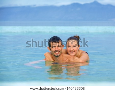 Smiling happy couple in geothermal mineral pool. Iceland