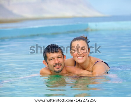 Smiling happy couple in geothermal mineral pool. Iceland - stock photo