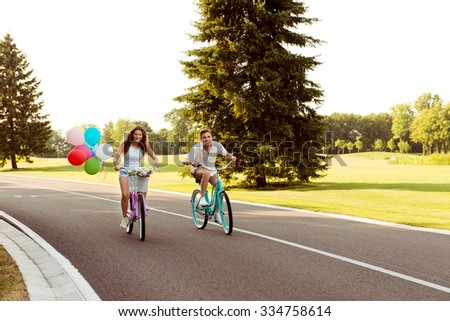smiling happy couple in love ride bicycles have fun - stock photo