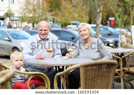 Smiling happy couple of seniors, a man and his wife, are enjoying glass of cold beer sitting with their granddaughter at the open air terrace of cozy cafe in the city center on a warm sunny day - stock photo