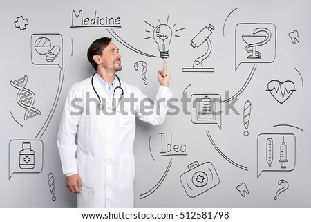 Smiling happy doctor pointing on bulb.