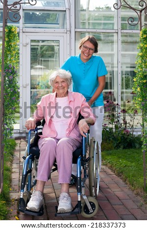 Smiling happy elderly lady in a wheelchair posing with an attractive young care assistant in front of the care home on a bricked pathway