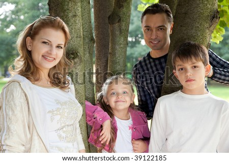 smiling happy family of four outdoors - stock photo