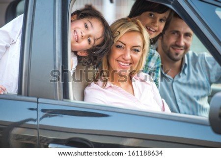 Smiling happy family sitting in automobile - stock photo