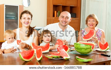 Smiling happy family together with watermelon over dining table