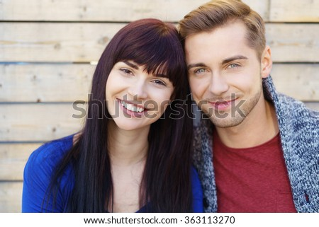 Smiling happy friendly young couple posing with their heads touching in front of a timber clad wall, head and shoulders close up - stock photo