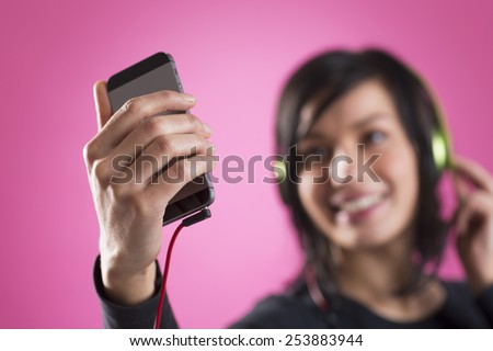Smiling happy girl enjoying listening to music with headphones and mp3 player, isolated on pink background. - stock photo