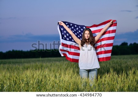 Smiling happy girl with developing the American flag. 4th july - Independence Day