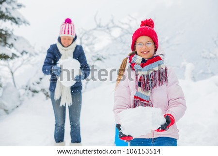 Smiling happy girl with her mother having fun outdoors on snowing winter day in Alps playing in snow. - stock photo