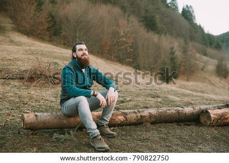 Smiling happy handsome man with beard in forest, mountains, park. Traveler Man relaxing . Travel Lifestyle hiking concept summer vacations outdoor. Bearded man.