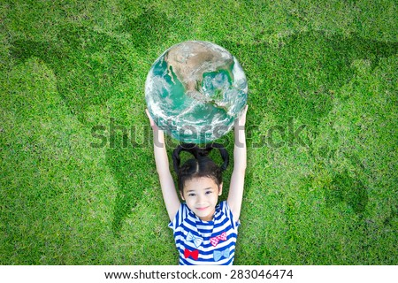 Smiling happy healthy little asian kid holding green globe lying on the world map grass: World environment day CSR concept of saving green sustainable ecosystems: Element of image furnished by NASA - stock photo