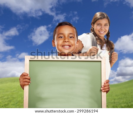 Smiling Happy Hispanic Boy and Girl In Grass Field Holding Blank Chalk Board. - stock photo