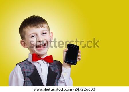 Smiling Happy, Joyful beautiful little boy holding mobile phone, looking at camera.Close-up Studio Portrait isolated on yellow background. - stock photo