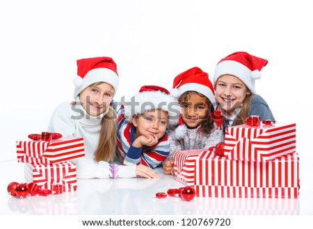 Smiling happy kids of four in Santa's hat with gift box, isolated on white - stock photo