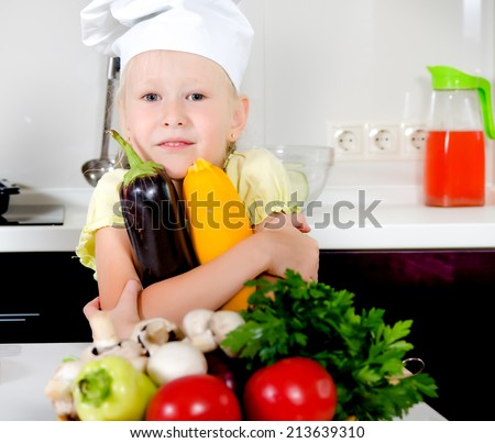 Smiling happy little girl in a cooks uniform standing in the kitchen grinning at the camera while holding fresh marrows in her hand with a bowl of fresh vegetables in the foreground - stock photo