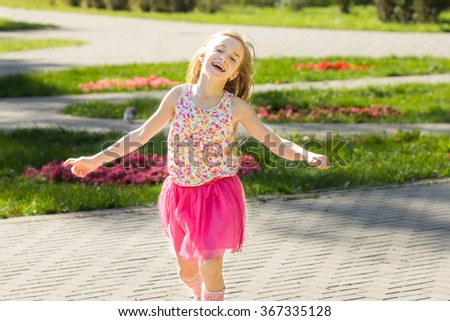 Smiling happy little girl in park running towards camera. - stock photo