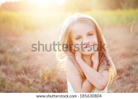 Smiling, happy little girl on a sunny summer meadow field - stock photo