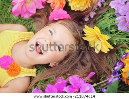 Smiling, happy little summer girl laying on the grass field with flowers - stock photo